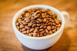 koffiebonen in cup op houten grunge achtergrond foto