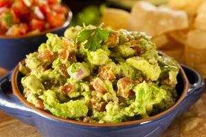zelfgemaakte biologische guacamole en tortillachips foto