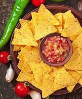 Mexicaanse nacho chips en salsa dip in kom foto
