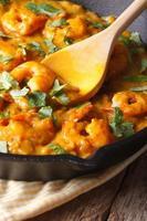 garnalen in currysaus in koekenpan macro. verticaal, rustiek