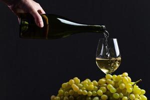 wijn wordt in een wijnglas gegoten foto