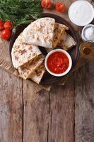 quesadilla gesneden en sauzen op een bord. verticaal bovenaanzicht