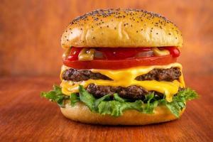 dubbele cheeseburger op rode tafel met rode achtergrond foto
