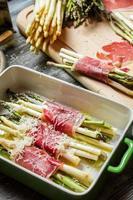 Bereiding van asperges omwikkeld met parmaham met kaas