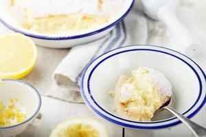 Citroenpuddingcake met verse citroenen. houten achtergrond