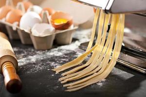 linguini-noedels worden geperst in een werkende keuken foto