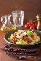 Italiaanse pasta spaghetti bolognese met basilicum op rustieke tafel