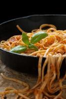 linguine met basilicum en rode saus in gietijzeren pan