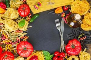 rauwe pasta met ingrediënten op zwarte bord foto
