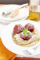 pasta met gehaktballetjes in tomatensaus, waterkers en parmezaanse kaas