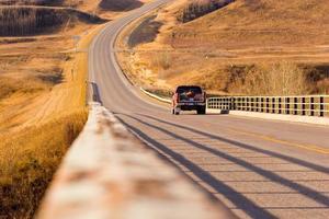 een rode vrachtwagen rijden op een lange landweg foto