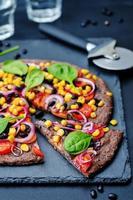zwarte bonen korst pizza met maïs, spinazie, tomaten, zwarte bonen foto