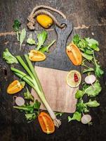 groenten en kruiden ingrediënten voor het koken rond lege snijplank foto