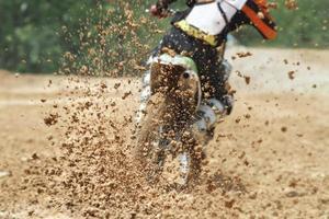 modderpuin dat uit een motorcrossrace vliegt foto
