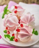 meringue koekjes in kom met room en granaatappelpitjes foto