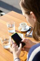 jonge vrouw te typen op de mobiele telefoon foto