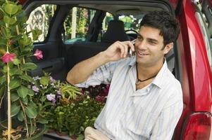man met behulp van mobiele telefoon op kwekerij foto