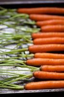 wortelen op metalen plaat horizontaal met stengels foto