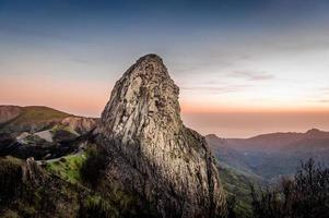 hoge rots bij zonsondergang foto