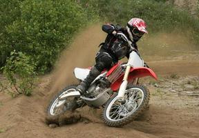 een crossmotorrijder die door het vuil rijdt foto