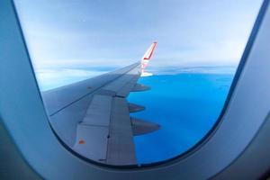 vleugel van het vliegtuig vliegt boven de wolken aan de hemel foto