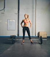 fit jonge vrouw op sportschool met barbell foto