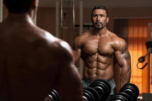 bodybuilder die bicepsen uitoefenen die eigen bezinning bekijken