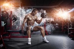 bodybuilder die de oefening van de bicepsenkrul met domoren doen