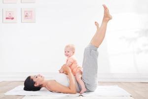 moeder doet gymnastiek met haar baby foto