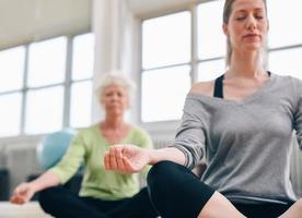 ontspannen fitnessvrouwen die yoga uitoefenen bij gymnastiek foto