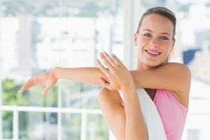 sportieve jonge vrouw handen uitrekken op yogales foto