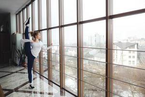 moeder maakt super hoge been stretch in de sportschool foto