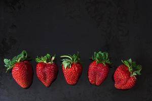 rode aardbeien in een rij over zwart foto