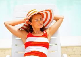 ontspannen jonge vrouw die op chaise-longue legt foto