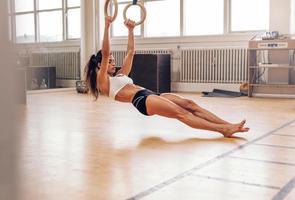 jonge geschikte vrouw die op gymnastiek- ringen omhoog trekt foto