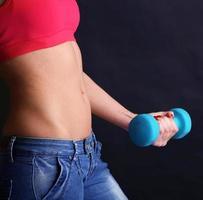 jonge mooie fitness meisje uitoefenen met halters geïsoleerd op zwart foto