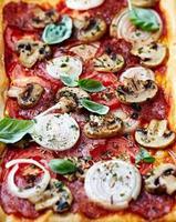 pizza met salami, tomaat en champignons foto