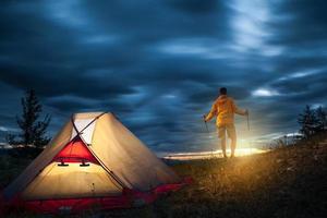 man op camping bij zonsopgang foto