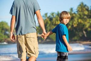 gelukkige vader en zoon samen wandelen op het strand