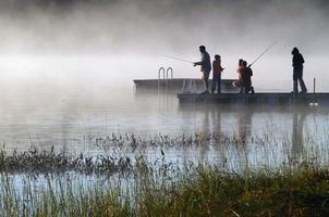 familie vissen vroeg in de ochtend op een mistig meer. foto