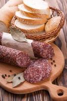 Italiaanse salami gesneden op houten tafel foto