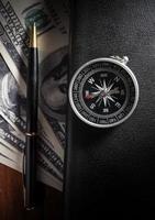 kompas op boek met pen en geld. foto