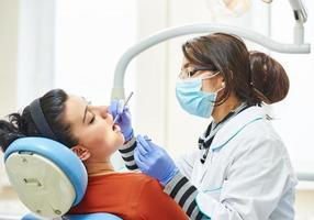 vrouwelijke Aziatische tandarts arts op het werk foto