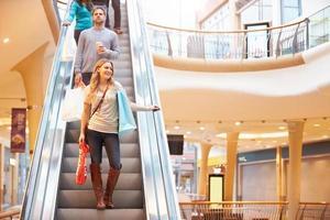 vrouwelijke shopper op roltrap in winkelcentrum foto