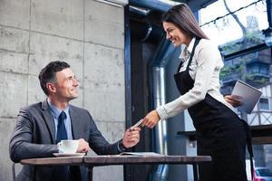 man die bankkaart geeft aan vrouwelijke ober foto