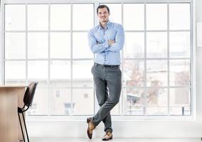 vertrouwen zakenman permanent in kantoor. succesvolle zakenman foto