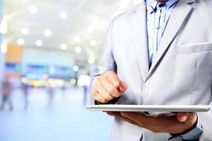 knappe jonge man in winkelcentrum met behulp van mobiele tablet