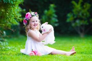 schattig meisje speelt met echte konijntje foto