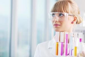 vrouwelijke onderzoeker die een reageerbuis in laboratorium steunt foto