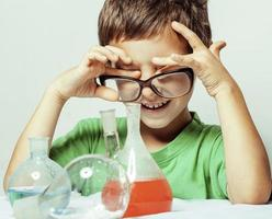 kleine schattige jongen met geneeskunde glas geïsoleerd foto